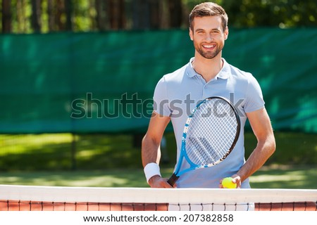 Great day to play! Cheerful young man in polo shirt holding tennis racket and ball while standing on tennis court