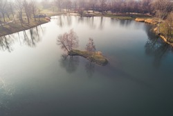 great drone view of a beautiful small island in the middle of a small frozen deep blue lake