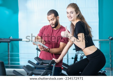 Great fitness workout. Athletic girl pedaling on a stationary bike in the gym while trainer on the tablet shows how to pedal. Girl showing thumbs up