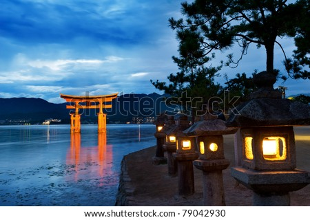 Great floating gate (O-Torii) on Miyajima island near Itsukushima shinto shrine, Japan shortly after the sunset with lit lanterns on the shore - stock photo