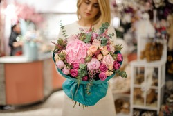 great flower bouquet of hydrangea roses peonies and green branches of eucalyptus wrapped in turquoise wrapping paper in woman hands