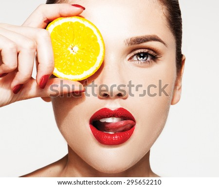 Great food for a healthy lifestyle. Beautiful young shirtless woman with red lips and manicure holding piece of orange in front of her eye while standing against white