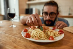 Great food. Young man, cook serving garlic butter shrimp pasta, decorating plate with basil and tomatoes. Cooking at home, Mediterranean cuisine concept. Selective focus on meal. Horizontal shot