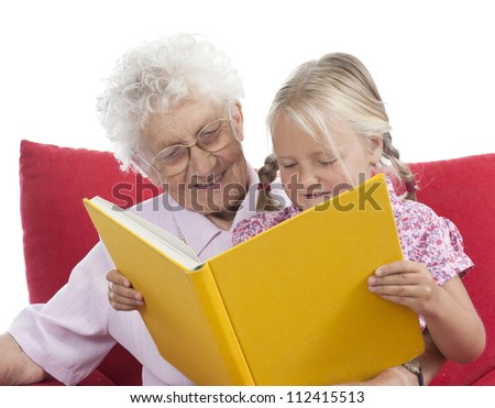 great grandmother and great granddaughter reading a book together