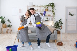 Great house cleaning together and rock band. Cheerful husband plays on broom, wife in apron sings in imaginary microphone in mop, in interior of modern living room with cleaning supplies, free space