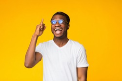 Great Idea. Excited Black Man Pointing Finger Up Having Eureka Moment Standing Over Yellow Background. Studio Shot