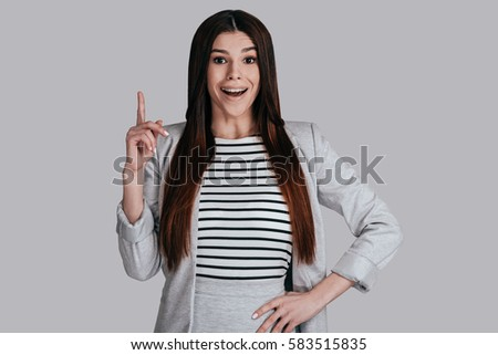Great idea! Gorgeous young woman in smart casual wear keeping finger raised and looking at camera with smile while standing against grey background
