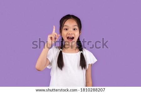 Great Idea. Little Asian Girl Pointing Finger Up Having Eureka Moment Posing On Purple Background In Studio Сток-фото ©