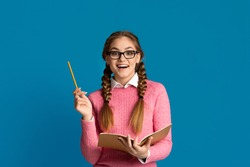 Great idea. Surprised teenager girl in glasses holds pencil and notebook in hands, isolated on blue background, studio shot