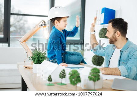 Great job. Cheerful little boy in a white hard hat sitting on the top of the table in his fathers office and giving him a high-five while the father working