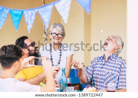Great laughs for a group of adult and senior people with a teenager enjoying a funny picture on the mobile phone. Group of family generation. Bright background. BBq time