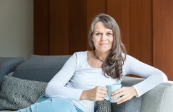 great looking middle aged woman having a calm morning and enjoying her coffee