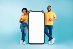 Great mobile app. African American couple pointing at giant smartphone with mockup, promoting application or website, advertising product or service, blue background. Full length