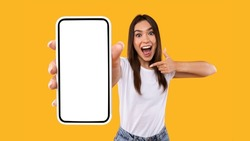 Great Mobile Offer. Excited Lady Pointing Finger At Smartphone In Her Hand, Emotionally Reacting To New App, Overjoyed Millennial Woman Standing Isolated Over Orange Studio Background, Panorama