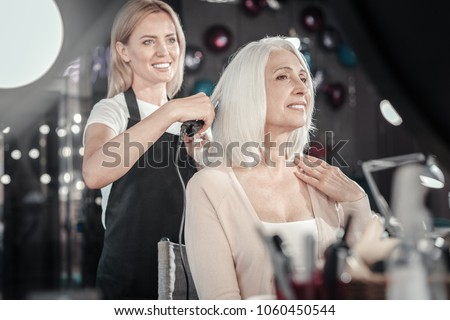 Great mood. Cheerful positive elderly woman looking at her reflection and smiling while being in a good mood