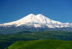 Great nature mountain range. Amazing perspective of caucasian snow mountain or volcano Elbrus with green fields, blue sky background. Elbrus landscape view - the highest peak of Russia and Europe