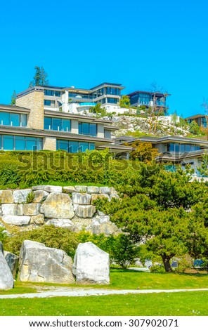 Great neighborhood with custom made luxury modern houses on the rocks with nicely landscaped front yards  in the suburbs of Vancouver, Canada. Vertical.
