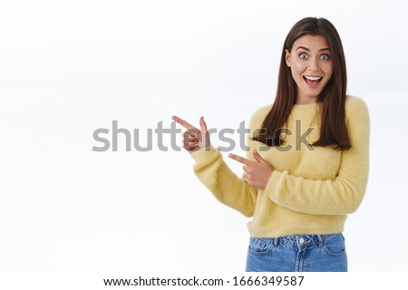 Great news hey take look. Excited happy and surprised beautiful young woman in yellow sweater turn yout attention at banner, pointing fingers left and scream joyful, stand white background