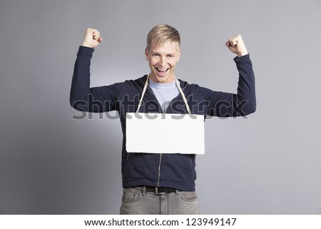 Great news: Joyful laughing man with raised arm showing success while presenting white blank signboard with space for text isolated on grey background.