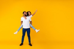 Great Offer. Full Body Length Of Cheerful African American Man Giving Piggy Back Ride For His Daughter, Little Girl Looking Aside And Pointing Fingers Up At Free Copy Space On Yellow Background