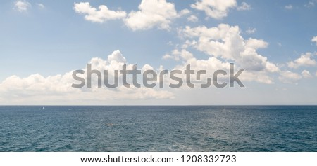 Great panoramic photo merge of the Ionian sea with boats and sky full of clouds.