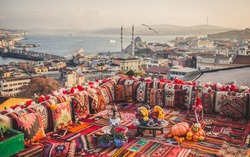 Great panoramic view of Istanbul from high terrace decorated traditional colorful ornamental pillows and carpets and stillife with fruits, turkish tea and hookkah