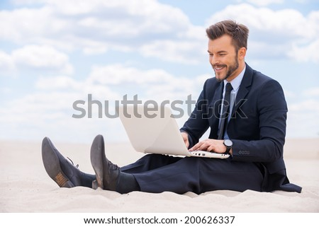 Great place to work. Cheerful young man in formalwear working on laptop while sitting on sand in desert