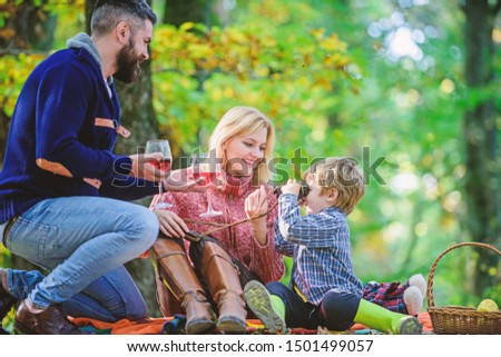 Great pleasure. Mother, father love their little boy child. Happy son with parents relax in autumn forest. Fall weather. Wine drinking. Spring mood. Happy family day. Family picnic. Warm day.
