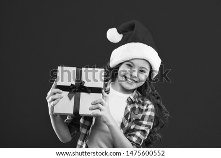 Great present. Present for Xmas. Childhood. Christmas shopping. New year party. Santa claus kid. Little girl child in santa red hat. Happy winter holidays. Small girl. This is for you.