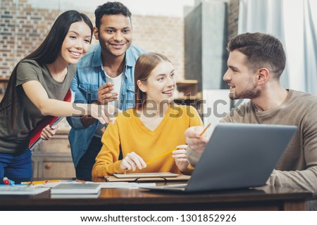Great proposition. Exuberant four students laughing and using laptop