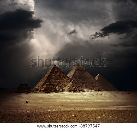 Great pyramids in Giza valley with dark clouds on the background