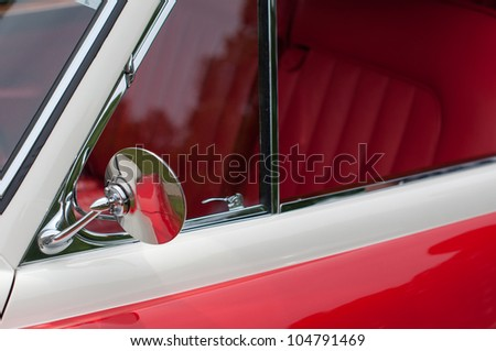 great red oldtimer vintage car detail: mirror and front seat row