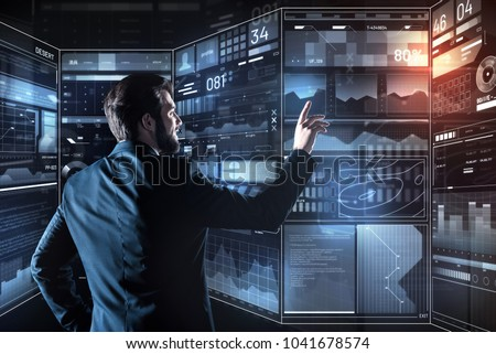 Great results. Clever skilled programmer smiling and feeling pleased while standing in a modern office and reading the information on a transparent futuristic screen #1041678574