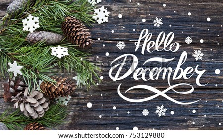 Great season texture with winter mood. Spruce branches, cones and snowflakes on old wooden rustic background. Nature december background with hand lettering