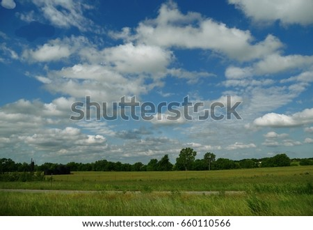 Great skies above the countryside  Beautiful cotton clouds hang above a green countryside   #660110566