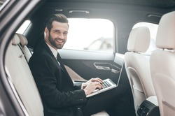 Great solutions every day. Confident young businessman working on his laptop and looking at camera while sitting in the car