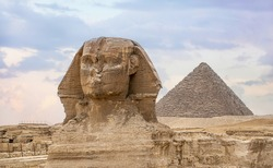 Great Sphinx and Pyramid of Khafre. ancient Egyptian civilization. Landscape with Egyptian pyramids. Ancient symbols and landmarks of Egypt for your travel concept to Africa in golden sunlight.
