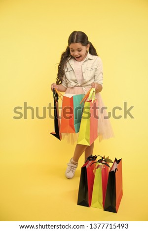 Great strategies to save on back to school purchases. Back to school season teach budgeting basics. Girl carries shopping bags. Prepare for school season buy supplies stationery clothes in advance. #1377715493