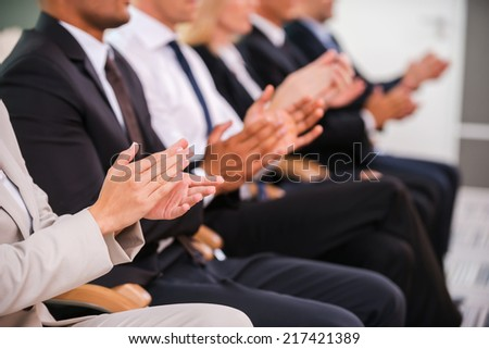 Great success. Group of business people clapping hand while sitting in a row