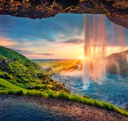 Great sunset on popular tourist destination - Seljalandsfoss waterfall, where tourists can walk behind the falling waters. Impressive summer scene of Iceland. Beauty of nature concept background.