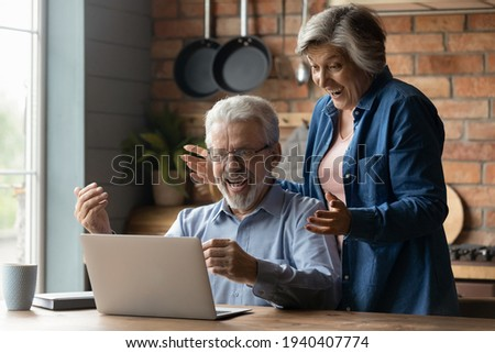 Great surprise. Overjoyed mature married couple on pension scream in delight getting unexpected news of prize award by email. Excited old age spouses read about cash reward in betting on laptop screen