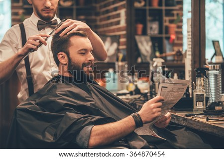 Great time at barbershop. Cheerful young bearded man getting haircut by hairdresser and reading newspaper while sitting in chair at barbershop
