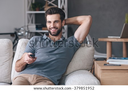 Great TV show.Handsome cheerful young man holding remote control and watching TV while sitting on the couch at home