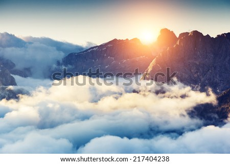Great view of the foggy Val di Fassa valley with passo Sella. National Park. Dolomites, South Tyrol. Location Canazei, Campitello, Mazzin. Italy, Europe. Dramatic scene. Beauty world. #217404238