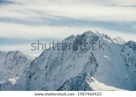 Great view to high snowy mountain wall with peaked top under cirrus clouds in sky. Alpine landscape with big snow covered mountains with sharp pinnacle in sunshine. White-snow pointy peak in sunlight. Stockfoto ©
