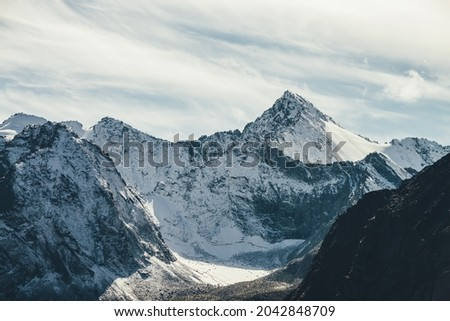 Great view to high snowy mountain wall with peaked top under cirrus clouds in sky. Alpine landscape with big snow covered mountains with sharp pinnacle in sunshine. White-snow pointy peak in sunlight. Photo stock ©