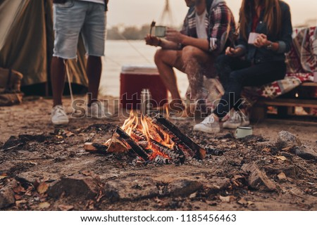 Great warm evening. Close up of young people eating roasted marshmallows while camping near the lake
