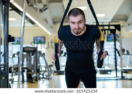 Great workout. Handsome fitness sportsman is having workout with stripes in fitness gym