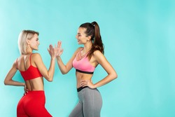 Great workout. Two young and happy sporty girls in sportswear giving each other high five while standing against blue background