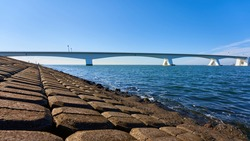 Great Zeeland Bridge, dam made of stone blocks, deep blue sea water and cloudless sky. Netherlands, Zeeland.